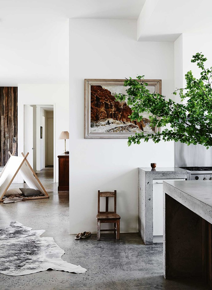 "Concrete is a strong feature in the house, covering the floors and benchtops in the kitchen and living areas. The landscape painting by Charles Bush was inherited from Claire's grandfather. The children's TV room, seen with the pitched tent, can be sealed off from the rest of the house with [sliding doors](https://www.homestolove.com.au/choosing-dual-purpose-doors-and-windows-1736|target=""_blank"")."