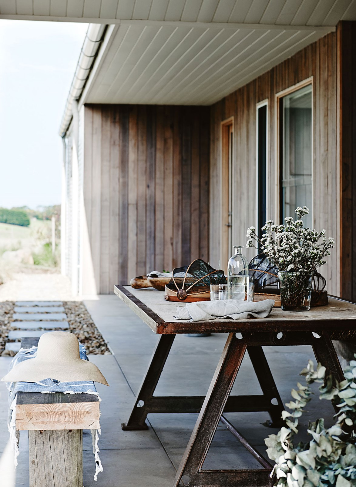 "The outdoor dining area on the verandah of this [timber and concrete farmhouse](https://www.homestolove.com.au/designer-dream-home-in-freshwater-creek-victoria-13657|target=""_blank"") is ideal for a casual breakfast or a long lunch, with the extended roof providing ample shade from the summer and a fire pit nearby to keep you warm in winter."