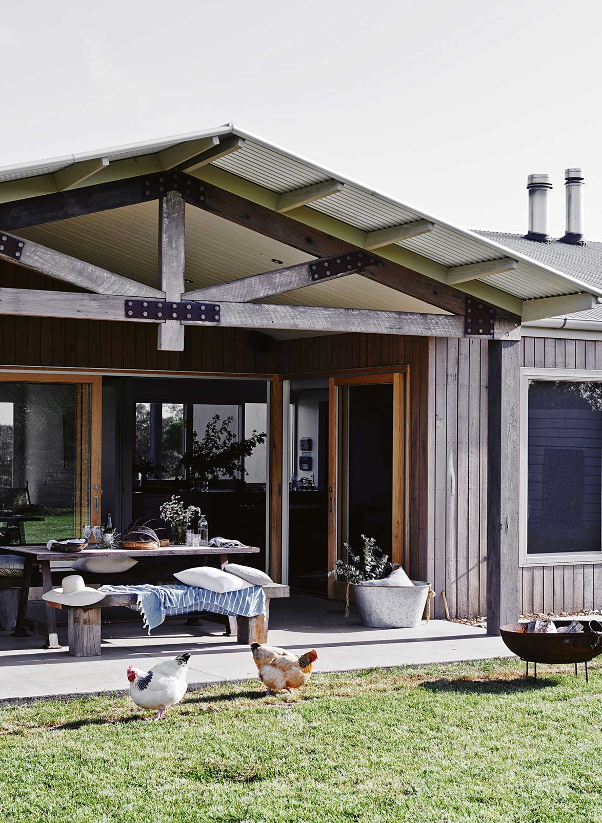 "Reclaimed timber frames an impressive back verandah at a [newly built home in Freshwater creek](https://www.homestolove.com.au/designer-dream-home-in-freshwater-creek-victoria-13657|target=""_blank""). A brood of chooks scan the lawn for signs of food. *Photo: Lisa Cohen / Stylist: Tess Newman-Morris*"