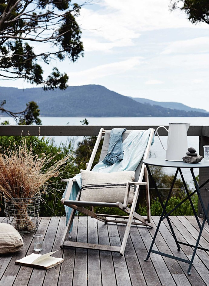 A deckchair and table create a spot to unwind and shuck oysters on the deck.