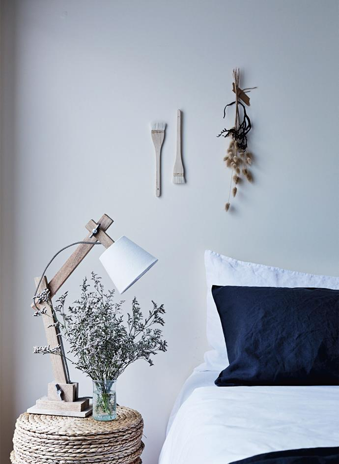 """Take a cue from the [farmhouse styling](https://www.homestolove.com.au/decorating-101-farmhouse-rustic-style-4345 target=""""_blank"""") and instead of giving everyday items the brush off, try turning them into wall art instead. The quirky touches are highlighted by the simple light and bed linen."""