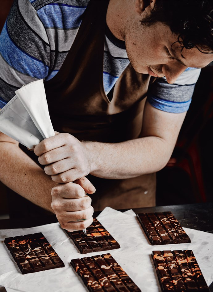 Zach Kennedy pipes orange onto a dark chocolate bar.   Photo: Lisa Cohen