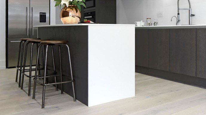 This monochrome kitchen island makes a small space look bigger by giving the impression of negative space.   | Photo: Alamy