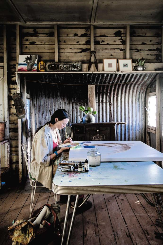"""Laura in the shearing shed she transformed into her studio. """"I love the starkness of it,"""" she says. """"The kids come up and visit on their bikes or horses. Sometimes you go in and a rabbit flies out — and the bulls are often just outside the window in the shade."""""""