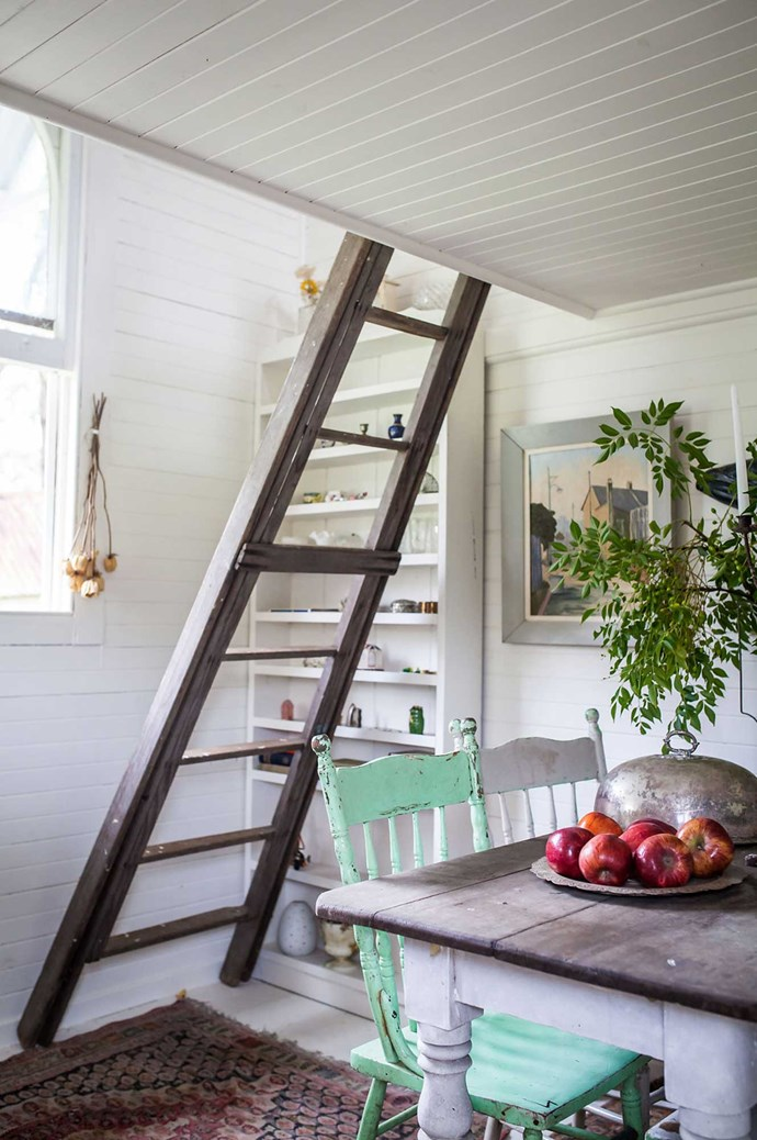 "The cabin is [a minimalist's dream](https://www.homestolove.com.au/how-to-be-a-minimalist-6322|target=""_blank"") - just a sitting room downstairs with a bedroom up the ladder. The kitchen table sits under the ladder, a space for Elsie to work, eat and read. There's an old-fashioned outhouse outside. Image courtesy of [Hunter Hunter](http://www.hunterhunter.com.au/