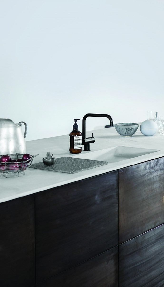 Norm Architects reinvented this IKEA flat-pack kitchen by employing designs by Reform, who specialise in custom counters and cabinet fronts that work with IKEA kitchen skeletons. The slick 18mm-thick counter was made to order from concrete, with an integrated sink and square lavastone workboard.