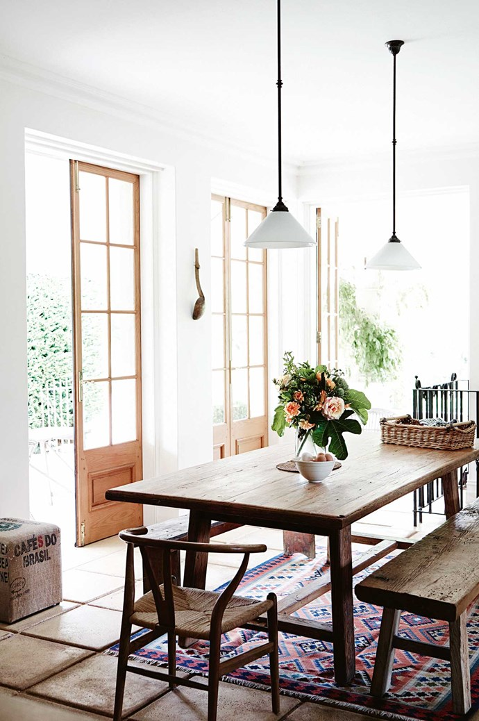 The long antique Chinese elm table runs the length of a dining room flooded with light coming through French doors.  | Photo: Mark Roper