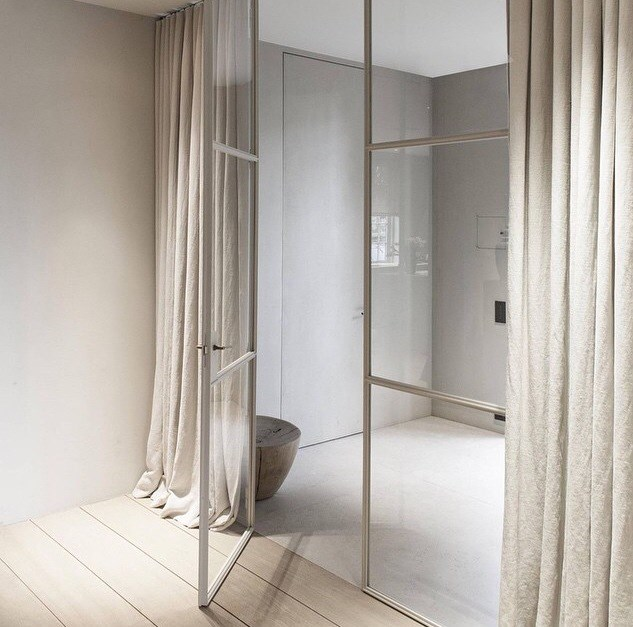 Double-height pivoting or French steel doors can be used to fill wide openings – and create flow – between rooms. Interior by Vincent Van Duysen.