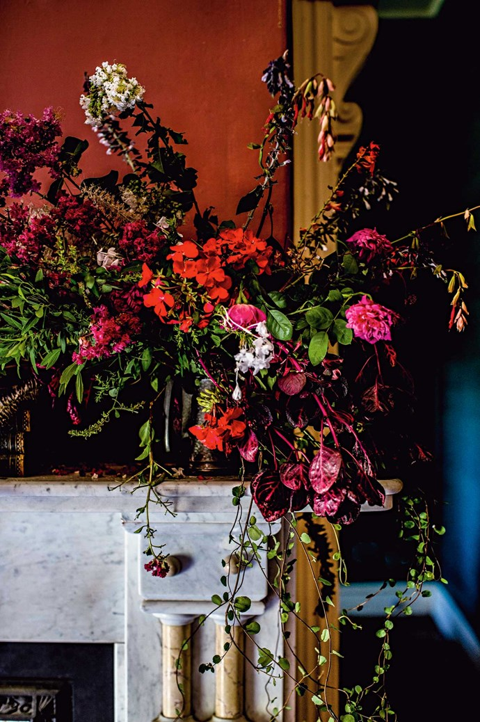 A cascade over the mantelpiece of crepe myrtle, geraniums, plumbago, roses, salvias and maidenhair vine. Stark lighting and rich colour throw Nick's interior styling to the cusp of surreal.  | Photo: Kara Rosenlund