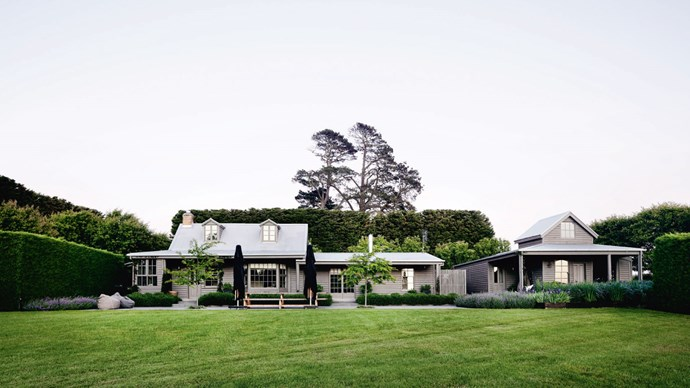 The house overlooks an expanse of lawn bordered by garden beds.