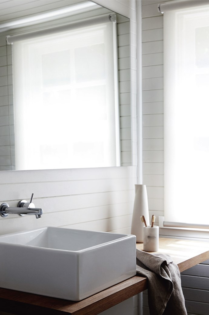 The spotless white bathroom has natural wood accents.