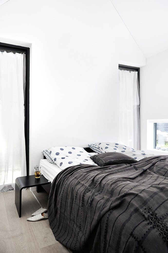 """Glass doors flank either side of the bed in the main bedroom. The house """"feels balanced"""" with one bedroom at either end of the house. 