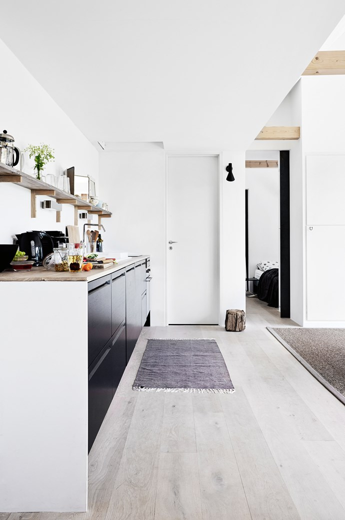 Open plan kitchen runs along a solid wall, with the door off the end leading to one of the two bedrooms. | Photo: Birgitta Wolfgang Drejer/Sister Agency