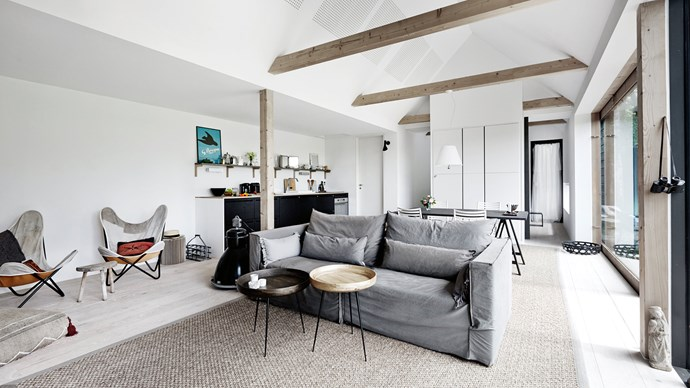 """These exposed beams in the living area have been left unpainted so that they will gradually turn silvery-grey and merge into the colour scheme. The easy chairs have been covered in fabric recycled from old military tents, which Hélène likes as a reflection of her """"nomad"""" lifestyle. 