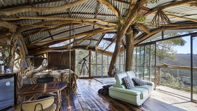 """In the Blue Mountains of New South Wales, the front door to Wollemi Wilderness cabin bares a scrawled message, """"SECRET TREEHOUSE. KEEP OUT, NO GROWN UPS."""" Designer Lionel Buckett has installed floor-to-ceiling windows that open up to untouched bushland, and equipped the cabin with a telescope for stargazing. _Image courtesy of [Airbnb](https://www.airbnb.com.au/rooms/3415111)_"""