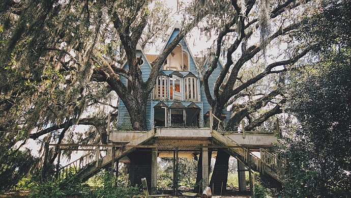 This abandoned treehouse mansion in South Florida, USA, was stumbled upon by urban explorer Drew Perlmutter. The Victorian gables and bay windows are draped in Spanish moss. _Image courtesy of [Drew Perlmutter](https://www.flickr.com/photos/sfldp/8047689947/)_