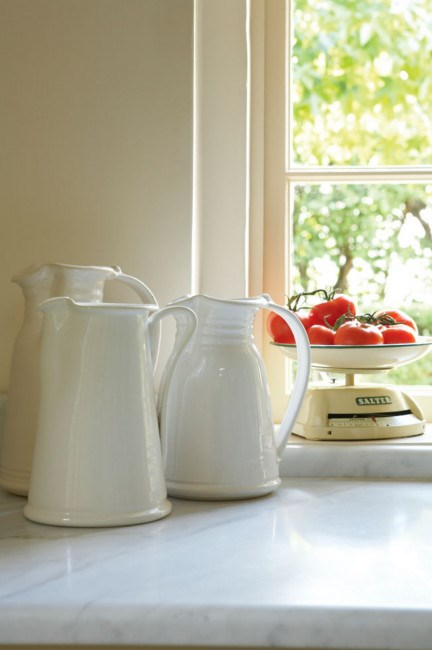 White glazed jugs and vintage scales decorate the kitchen window. | Photo: Michael Wee