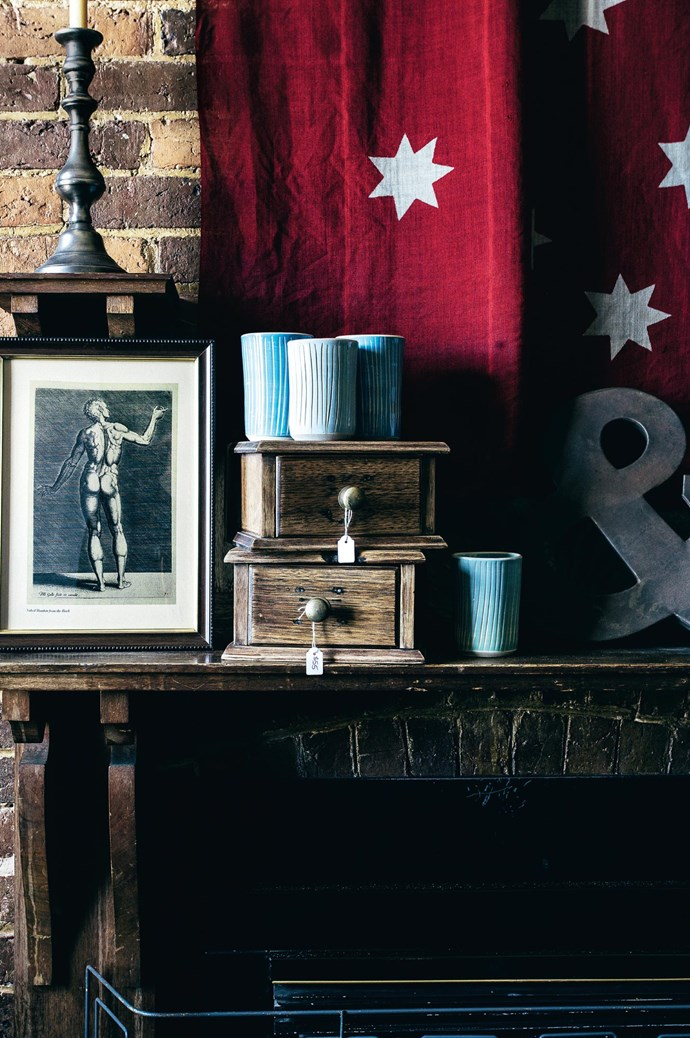 A vintage Australian ensign flag draped behind ceramic tumblers by [Adriana Christianson](http://adrianachristianson.com.au/), sitting on repurposed small drawers from a dismantled dressing table. Many of the furniture at The Black Hen is salvaged, refitted and resurfaced by Julie's husband Noel. | Photo: Felix Forest