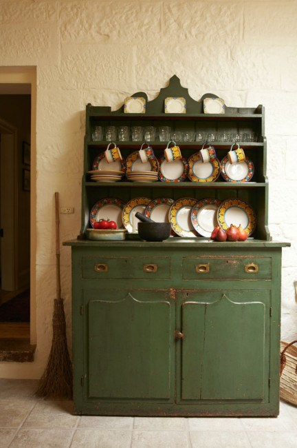 A green kitchen dresser storing porcelain and tea sets.  | Photo: Michael Wee