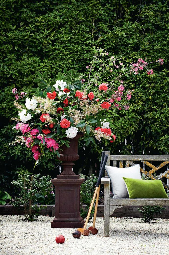 Flowers pour from a pedestal urn, bring a touch of grandeur and wild beauty to this formal garden.