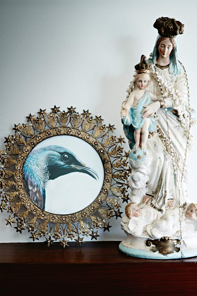A framed painting of a tui bird next to a second-hand religious statue.