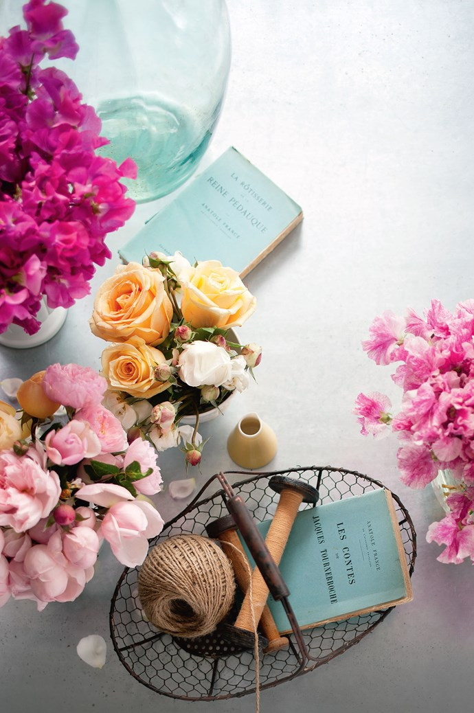 Blooms look fresh-faced beside salvaged antiques - like pewter dishes, copper tableware, wooden ornaments, even old books. These warm-hued posies contrast some vintage baby blue paperbacks. | Photo: Craig Wall