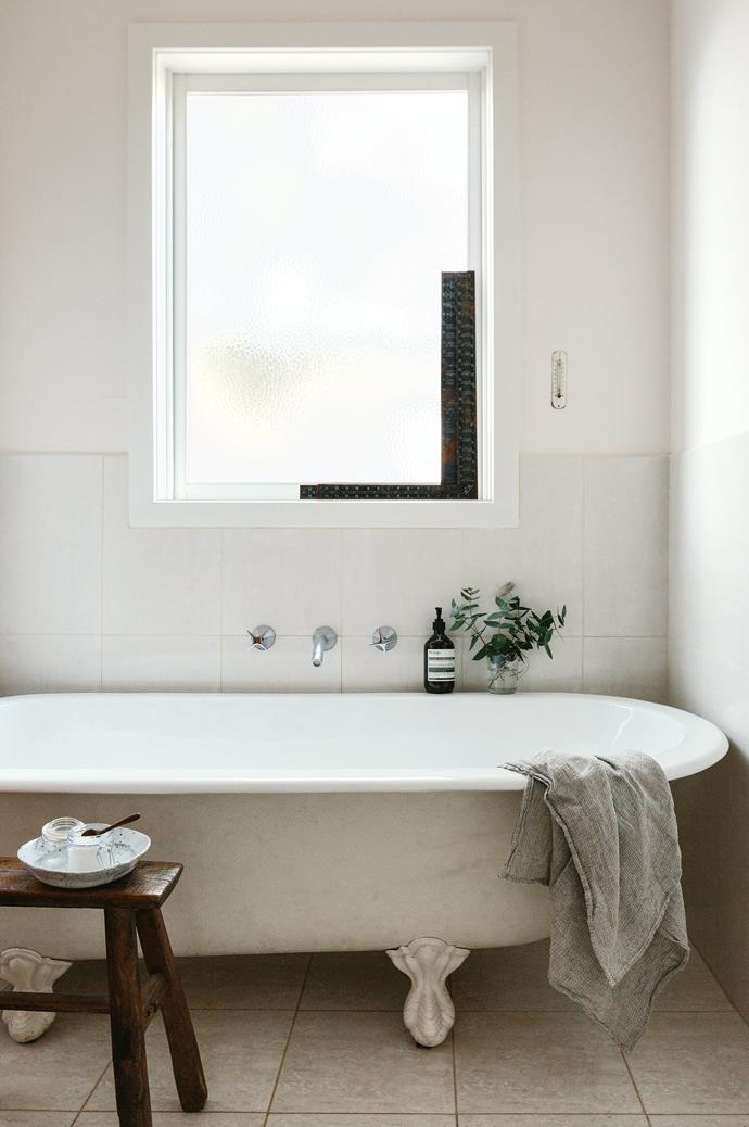 "The claw-foot [freestanding bath](https://www.homestolove.com.au/freestanding-baths-4520|target=""_blank"") is surrounded by a vintage stool, a French thermometer and rulers."