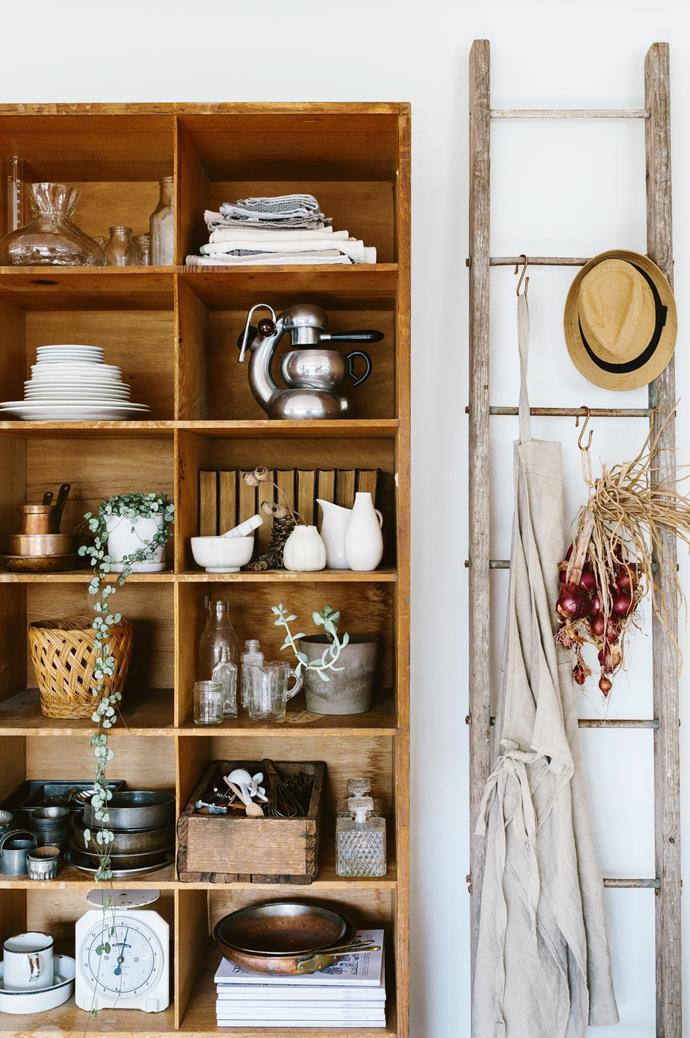 Each piece of furniture, either recycled or vintage, is well-worn in sentimental value. Old copper pans, encyclopaedias and glassware sit atop repurposed timber shelves from a hospital. An old ladder moonlights as a hanging rail for aprons and outerwear.