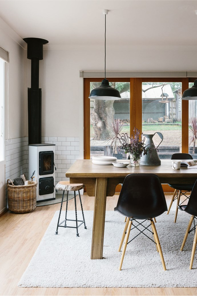 Vintage metal light shades were painted black to match the replica Eames chairs, which balance the neutral palette.