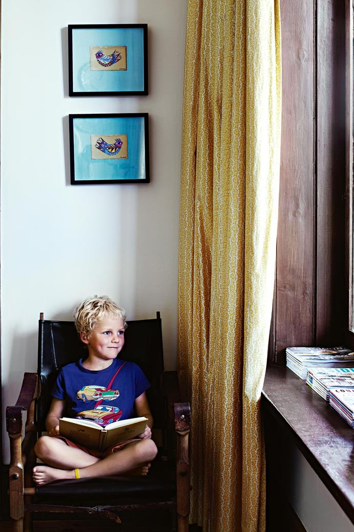 """Jock stakes out a reading spot under Anita Laurence's """"Little Birds"""" paintings."""