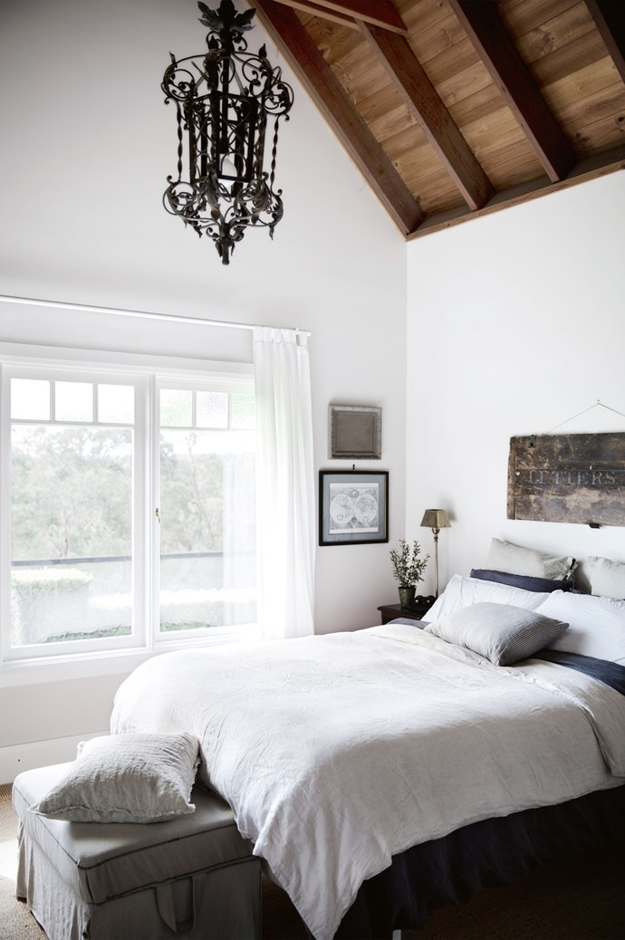 The master bedroom welcomes in natural light. Heidi painted the walls with Dulux Antique White USA, hung simple curtains and laid sisal carpet from [The Natural Floorcovering Centres](http://www.naturalfloor.com.au/). The rustic sign above the bed was found at [Mitchell Road Antique & Design Centre](https://mitchellroad.wordpress.com/).   Photo: Chris Warnes