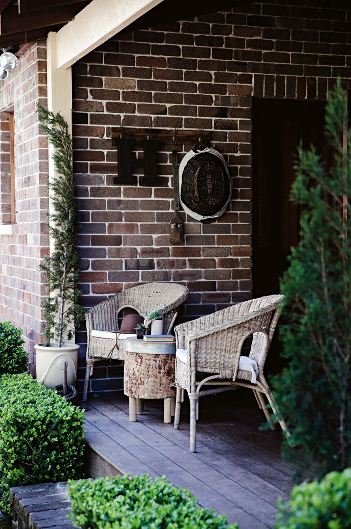"""Verandah chairs face the garden, the couple's ongoing """"labour of love."""" While tank water and gritty soil pose their challenges, Heidi and Jason toil on in shaping the land with structured hedges and specimen trees."""