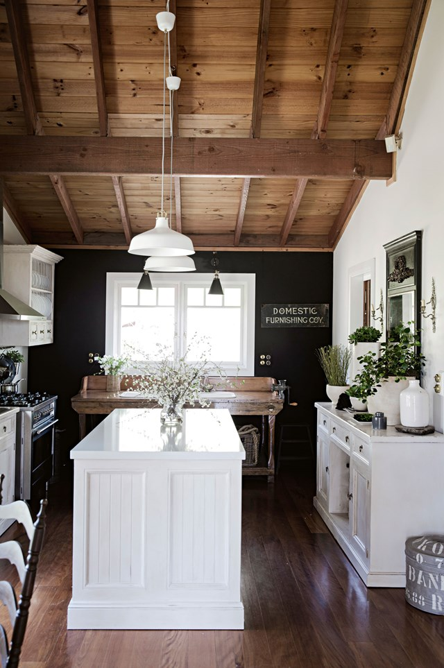 "This classic, French-style kitchen in a [rustic home on Sydney's outskirts](https://www.homestolove.com.au/fringe-benefits-a-rustic-intimate-home-on-sydneys-outskirts-12079|target=""_blank"") feels anything but stuffy, thanks to the addition of a black feature wall. Black is instantly modernising when used in spaces with high ceilings and plenty of natural light. White cabinetry and simple décor prevent the room from feeling closed-in. *Photo: Chris Warnes / Story: Country Style*"