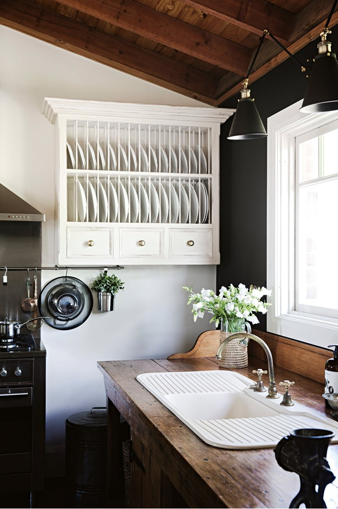 The kitchen features a vintage workbench fitted with a sink, resting beside a chalkboard wall.    Photo: Chris Warnes