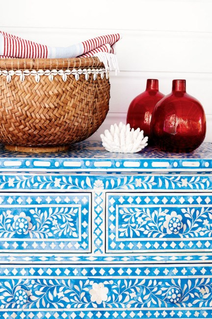 A chest of drawers with mother-of-pearl inlay is home to a woven basket, colourful vases and a trinket or two from the nearby beach.    Photo: Jared Fowler