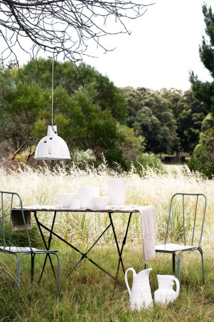 Team white tableware, raw linen and rustic furniture for a stylish mix inspired by nature's beauty. Metal garden chairs and an early French bistro folding table, covered with a handmade linen table runner. | Photo: Sam McAdam-Cooper