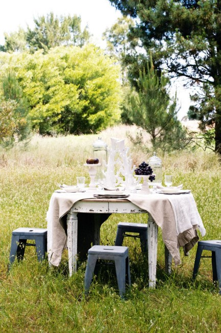 A raw linen tablecloth adorns a a two-leaf extension table and contrasts with the industrial-style zinc-coated garden stools. | Photo: Sam McAdam-Cooper