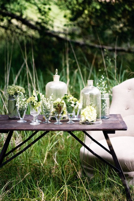 A trestle table decorated with glass jars, wine glasses and large domed glass bottles. | Photo: Sam McAdam-Cooper