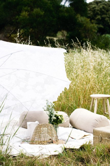 A lace parasol covers a comfortable white picnic setting. | Photo: Sam McAdam-Cooper