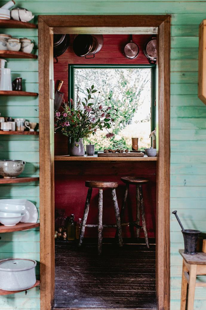 Looking from the kitchen into the pantry, with the couple's pottery cups and bowls — a mix of their own and others collected from their travels  — on display in floor-to-ceiling shelving.