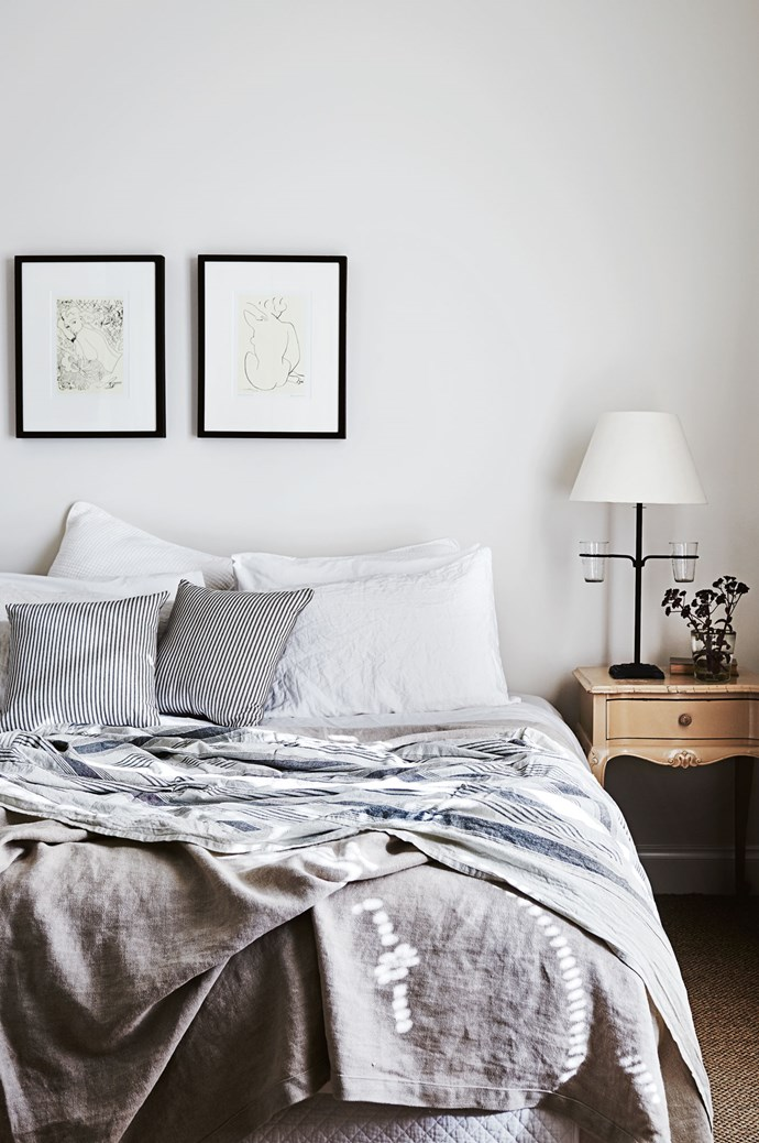 Layers of relaxed linen and a pair of minimalist artworks keep the master bedroom feeling modern.