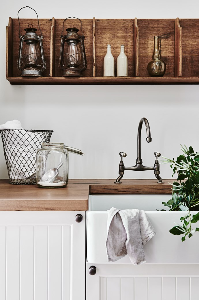 The kitchen features a ceramic farmhouse sink and timber benchtops.