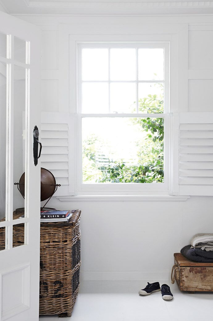 In the sitting room, a pair of plantation shutters can be flung open to let in natural sunlight while an old ammunition box has been re-purposed as storage for extra throw rugs.