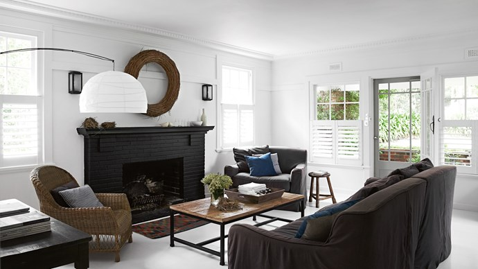 A brick fire-place painted in black is the focal point of the eclectic style living room.