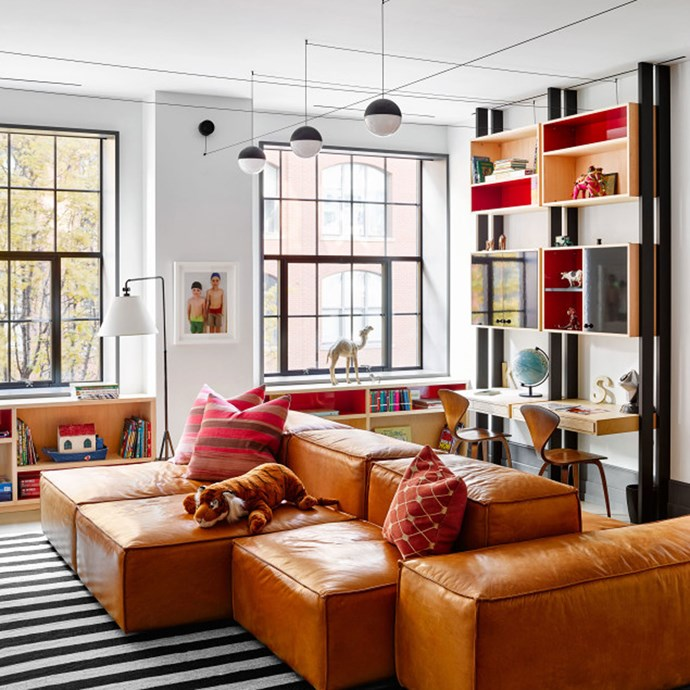 The boys' playroom is lined with shelves holding their toys, and divided by a leather sectional sofa.  | Photo: Architectural Digest