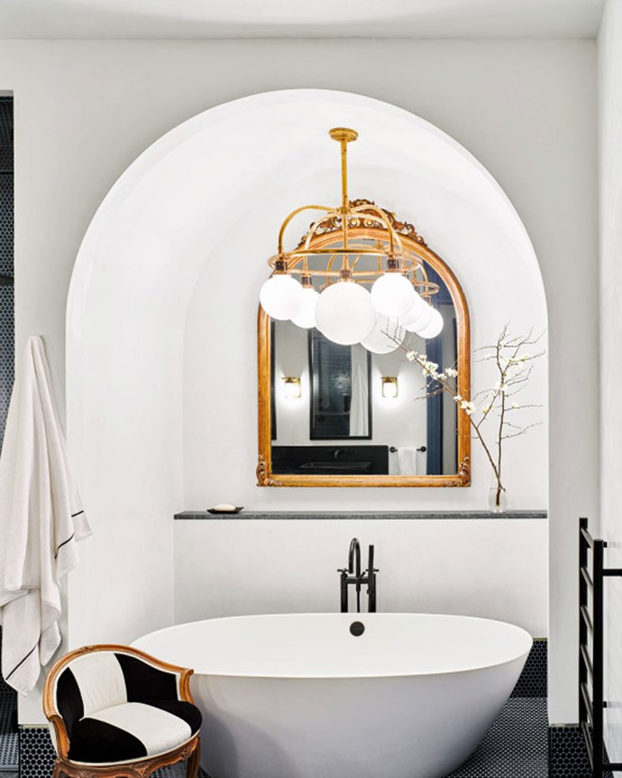 The bathroom sits across from the home gym, luxuriously embellished with gold-rimmed fixtures and a Victoria + Albert tub.  | Photo: Architectural Digest