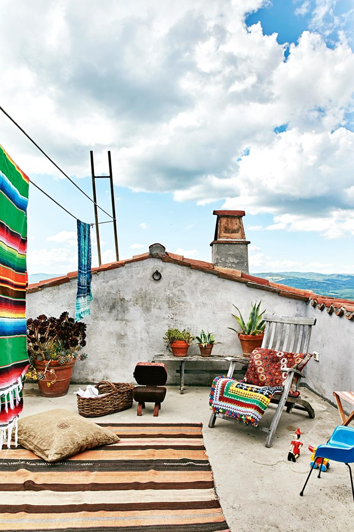 The rooftop garden is decorated with vibrantly coloured rugs, beach towels and an array of potted plants.