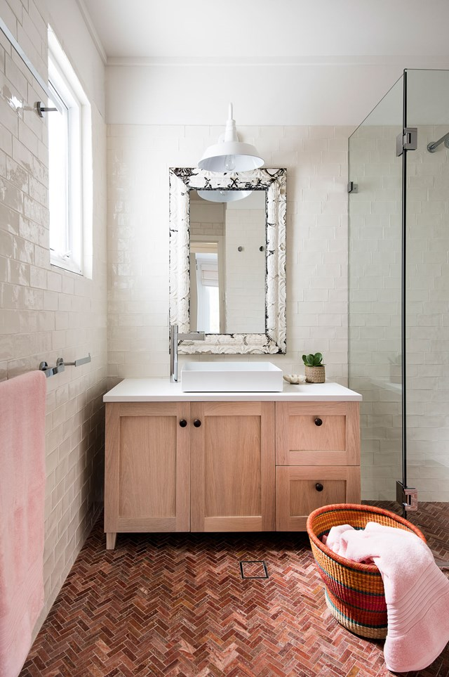 Terracotta tiles laid in a herringbone pattern add texture and warmth to this white bathroom.