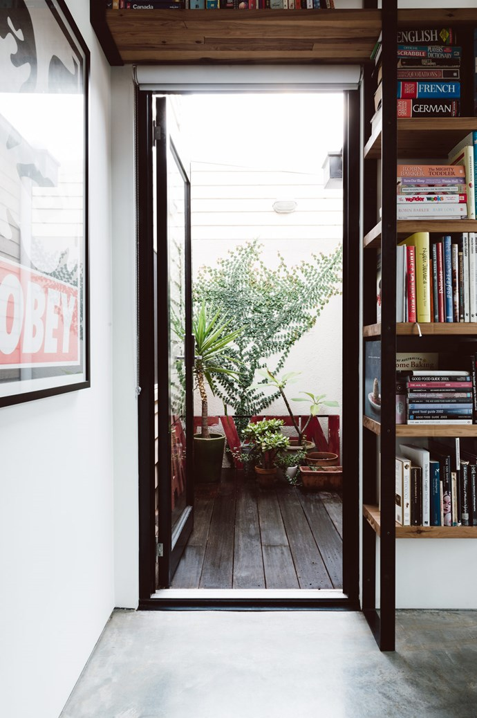 """""""We're really happy with the transition between the old section of the house and the new,"""" says Justin. """"The traditional central corridor arrives at a small vestibule screened from the living space by a open book shelf. It alters the path of travel slightly and allows the eye to adjust to the brightness of the sunlit living space."""" 