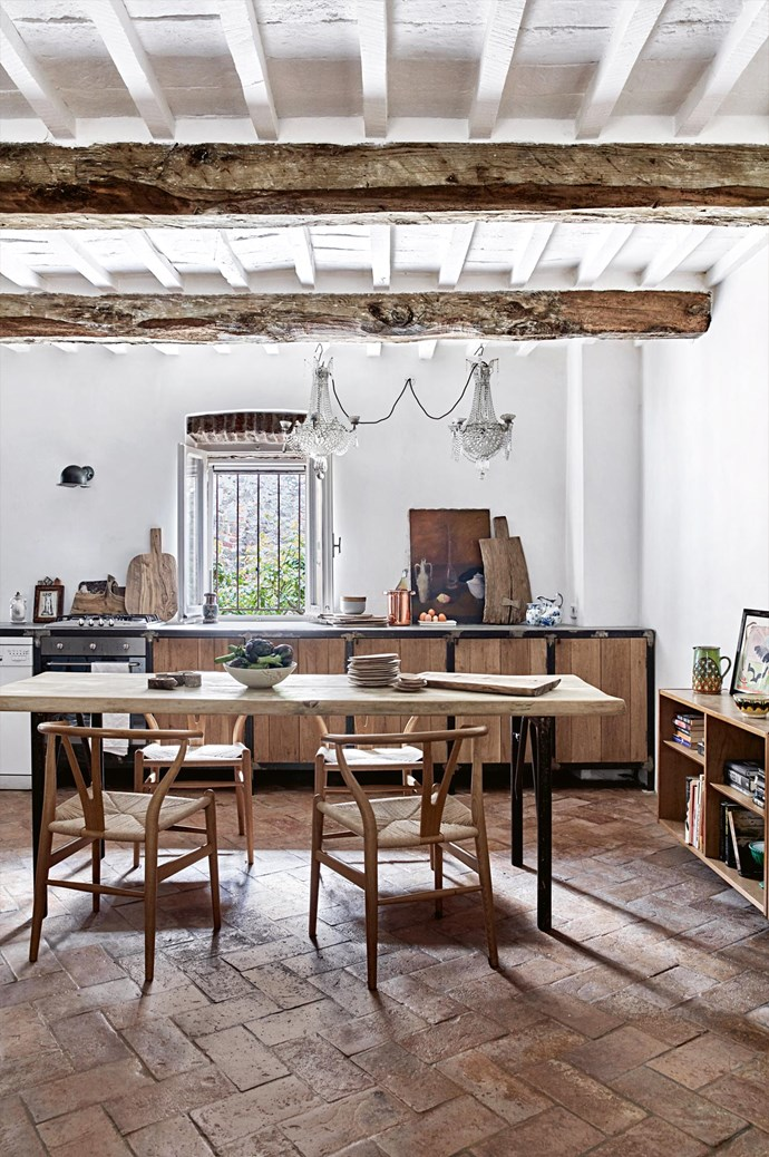 The rustic kitchen and dining room features brick floors, exposed wooden beams and a set of vintage Hans Wegner 'Wishbone' chairs.